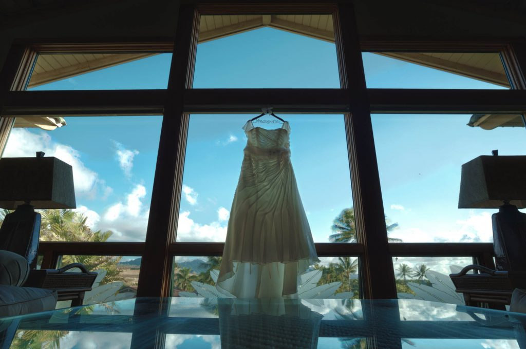 Wedding dress hung up in large living room window.