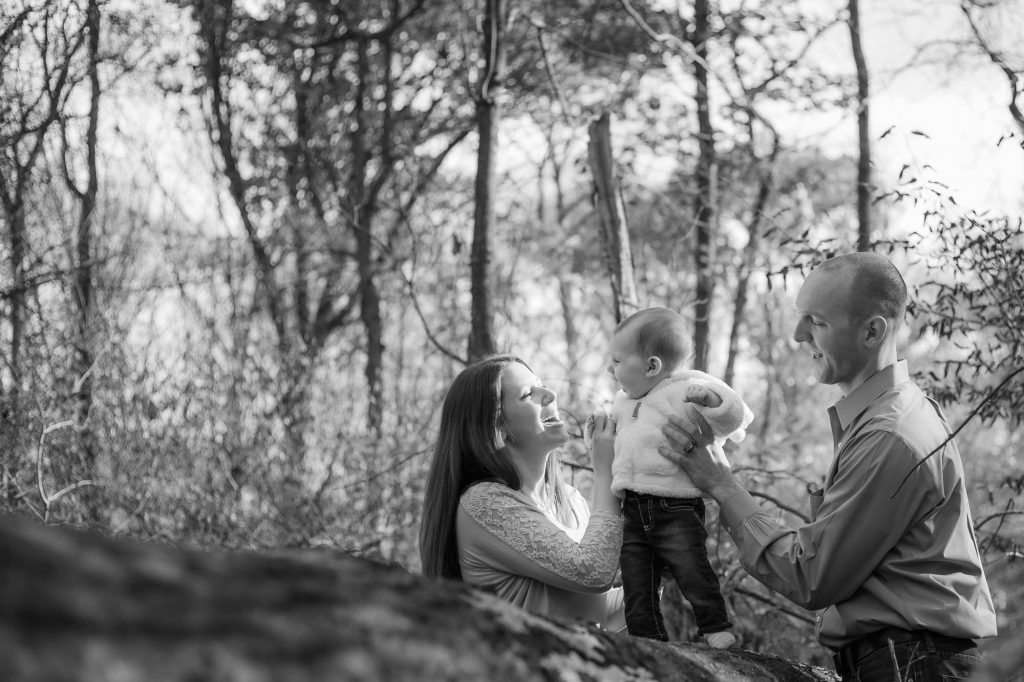 Parents and toddler in the woods.