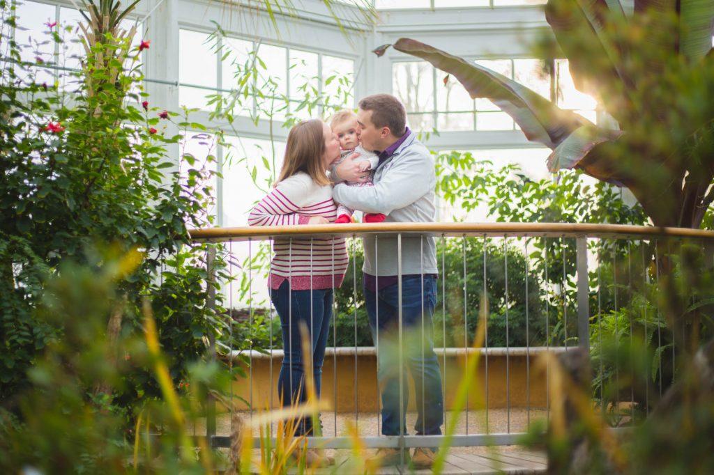 Parents kissing toddler.
